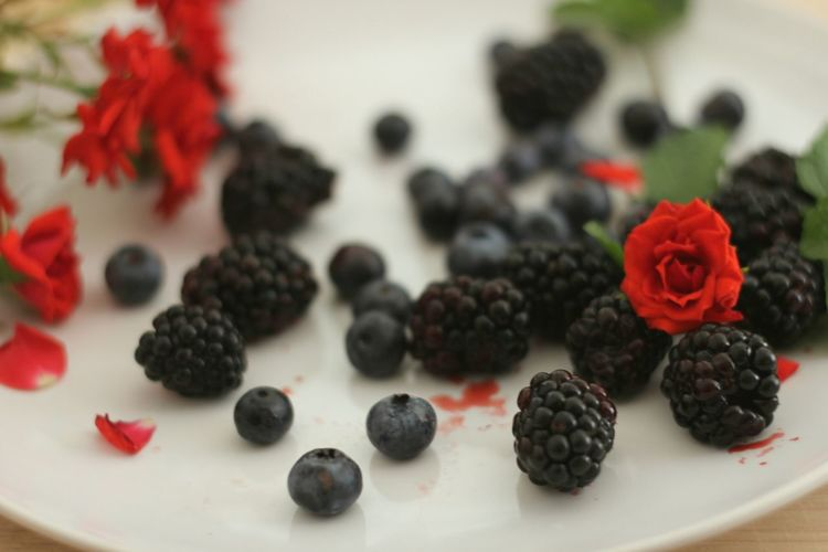 Close-up of berries with red roses on plate