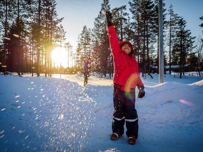 Boy Throwing Snow Against Trees During Sunset
