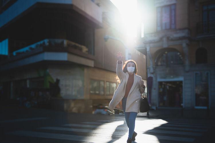Woman wearing mask walking on street in city