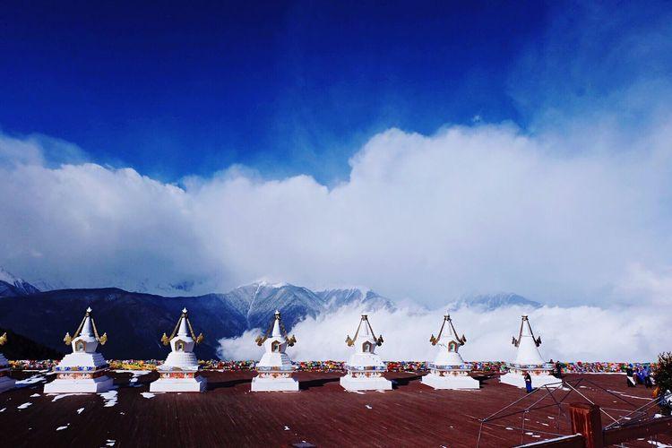 Stupas by snowcapped mountain against sky