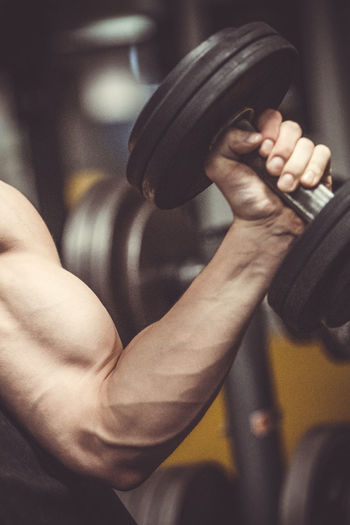 Cropped Hand Of Man Exercising With Dumbbell At Gym
