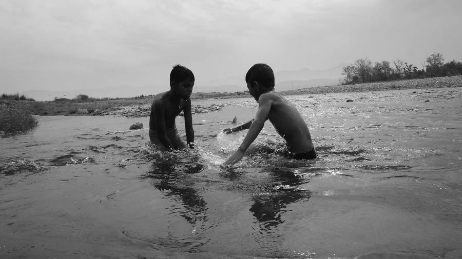 Boys having fun Ganges - II Bonding Boys Childhood Enjoyment Friendship Fun Funinwater Ganges Ghat Leisure Activity Love Outdoors Playing Real People Shirtless Sky Togetherness Water