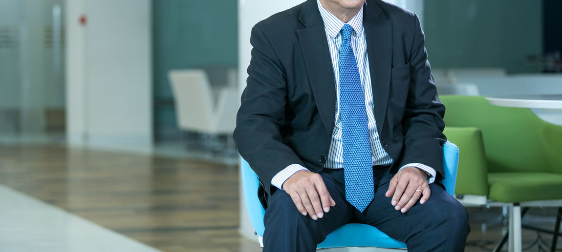 Midsection of man sitting on wall