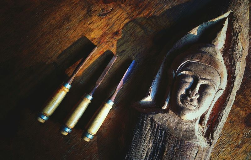 Sunlight and shadow on surface of Thai Buddha face on the old tamarind wood with wooden carving tools on wooden tabletop at workshop in vintage tone style Thai Handcraft Culture Traditional Old Vintage Retro Wood Craving Tools High Angle View Space Brown Art Buddha Face Vintage Tone Wood Wooden Craving Old Retro Antique Ancient Thailand EyeEm Selects Shadow Close-up Textured  Rusty Carving - Craft Product