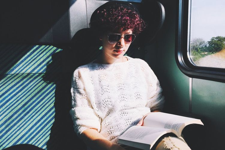 Young Woman Reading Book While Traveling Train During Sunny Day