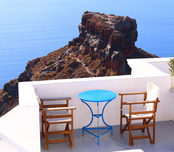 Table and chairs on rocks by sea against blue sky