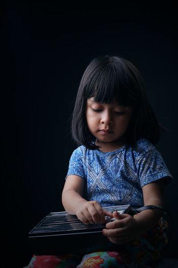 Cute girl holding radio against black background