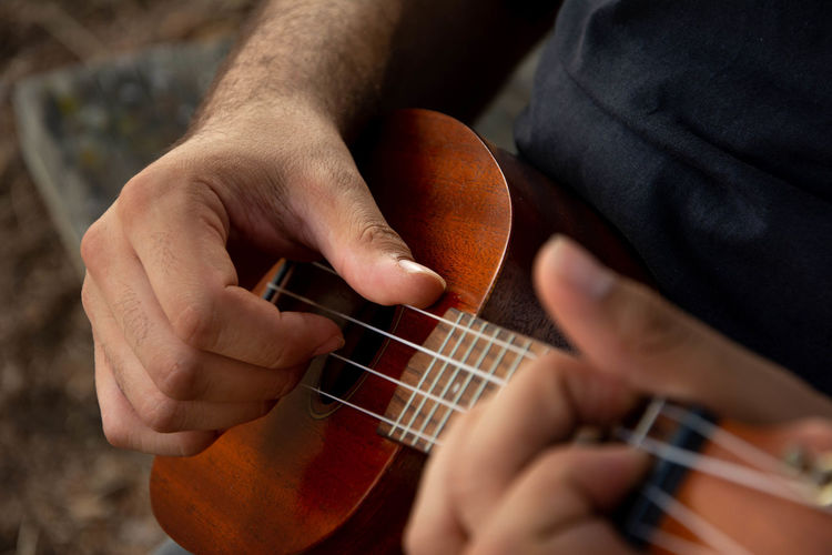 Cropped hand of man playing ukulele outdoors