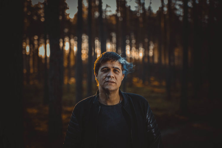 Mid adult man smoking in forest during sunset