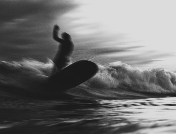 Person surfing in sea against sky
