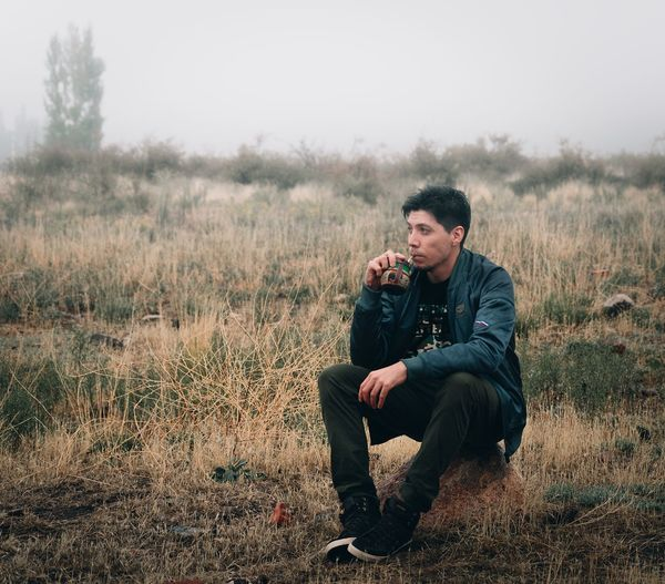 Young man photographing while sitting on land