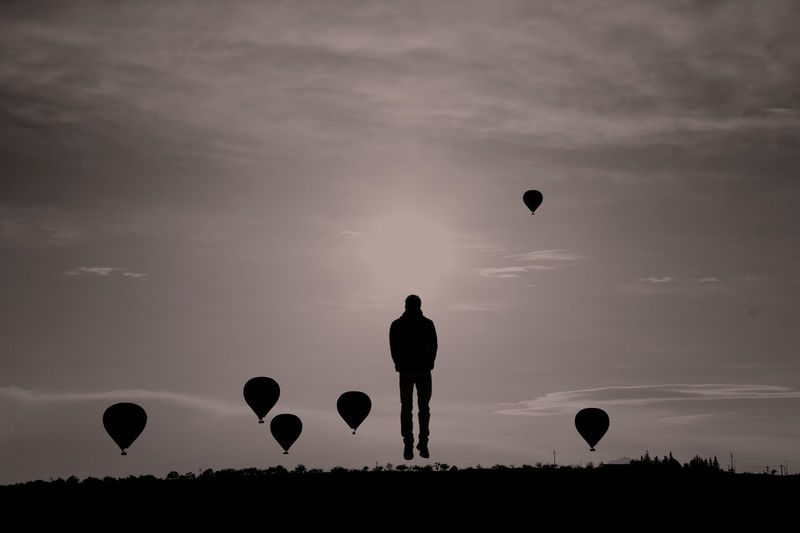 Silhouette Person Levitating By Hot Air Balloons Flying Against Sky During Sunset