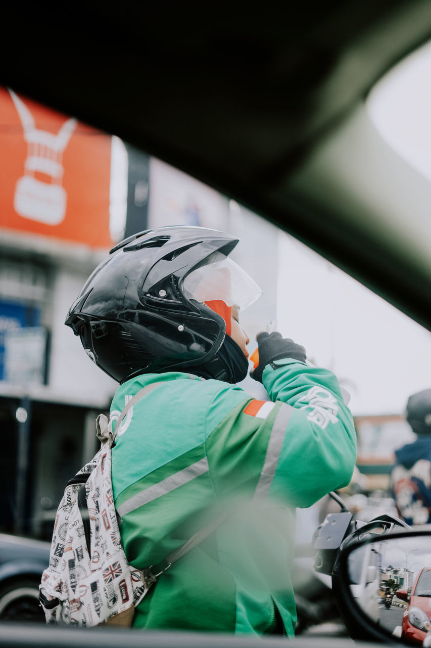 REAR VIEW OF MAN WORKING WITH MOTORCYCLE