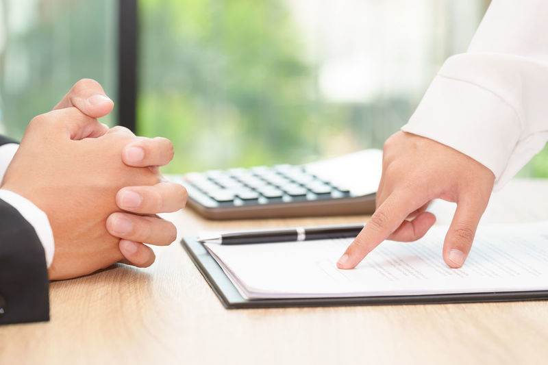Cropped hands of business coworkers discussing over document at desk