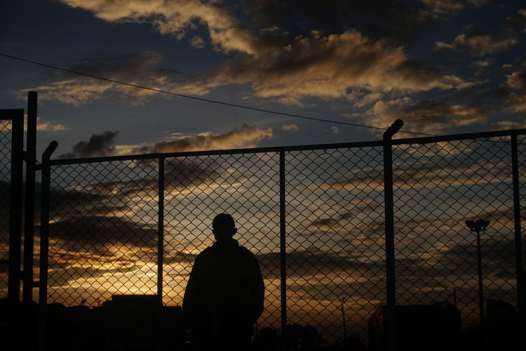 Silhouette man standing by fence against sky during sunset
