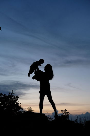 Silhouette couple standing against sky during sunset