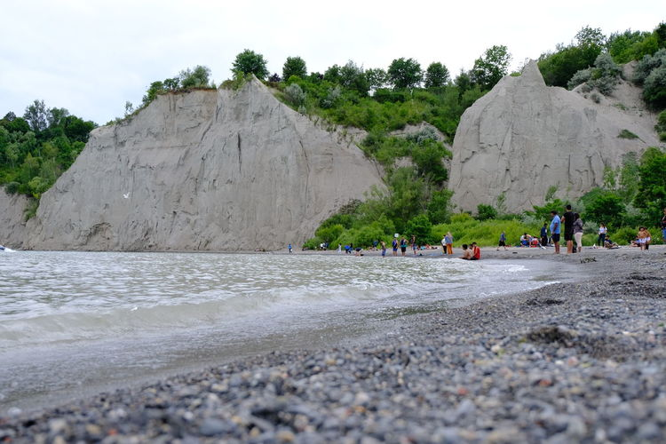 Surface level of rocks and people at beach against sky