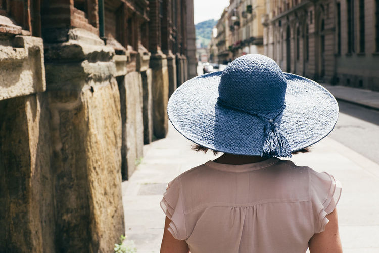 Rear view of woman with hat standing against building in city