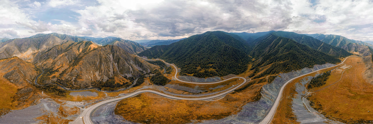 Stunning landscape of high mountains, highway, coniferous forest