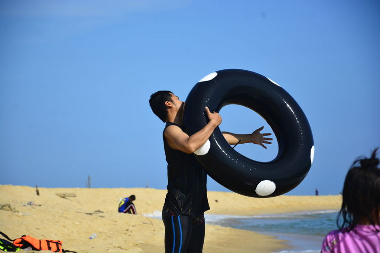Man holding inflatable ring on beach against sky
