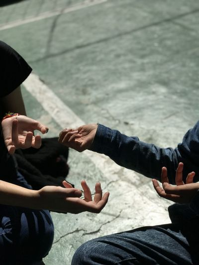 Cropped hands of friends gesturing while sitting on road