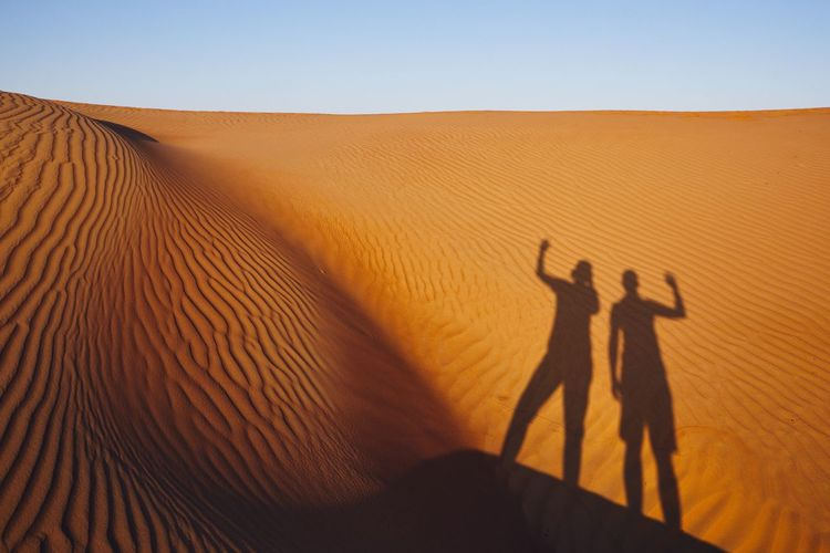Shadows of two friends waving on greeting. Sand dunes in Oman desert. Shadow Sand Dune Desert Landscape Nature Human Arm Sand Focus On Shadow Two People Scenics - Nature Sunlight Men Sky Waving Greeting Gesturing Friends Friendship Enjoyment Fun Happiness Vacations Oman Togetherness Discovery