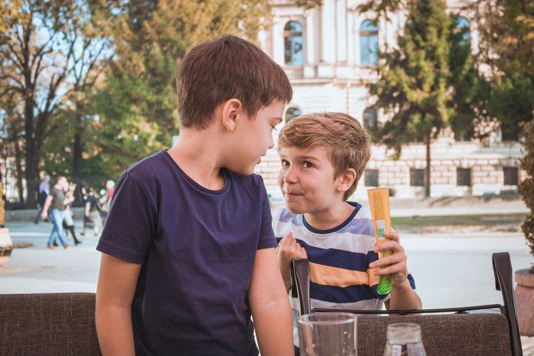Smiling siblings at sidewalk cafe