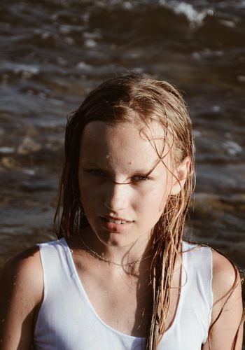 Close-up portrait of girl standing in sea