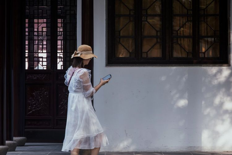 Young woman using smart phone standing by building