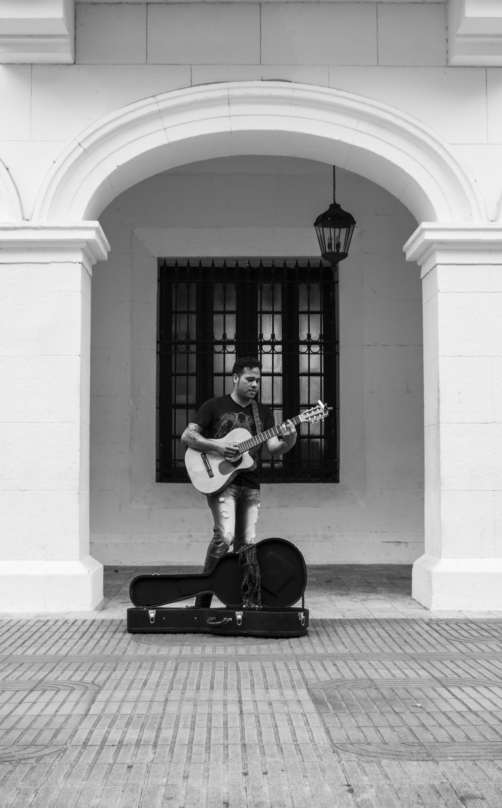 real people, full length, architecture, one person, building exterior, built structure, musical instrument, musician, lifestyles, playing, leisure activity, music, day, arch, performance, outdoors, arts culture and entertainment, guitar, skill, architectural column, men, young adult