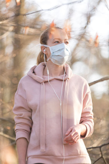 Woman wearing mask standing in forest