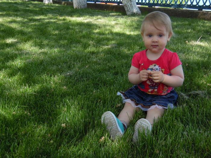 Portrait Of Girl Sitting On Grassy Field