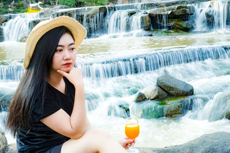 Woman with juice against waterfall