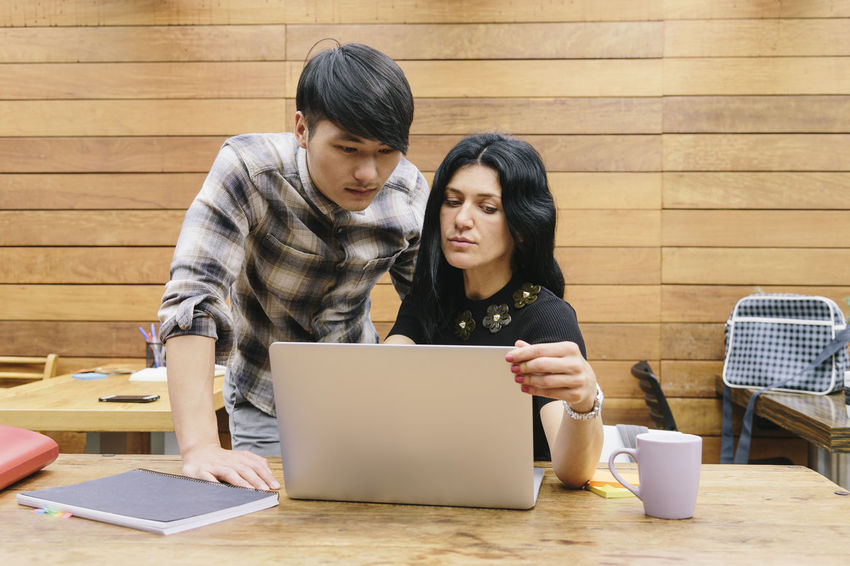 Coffee Couple Coworking Email Chinese Cup Of Coffee Internet Laptop Lifestyles Multiethnic Couple Notebook Partners Real People Small Company Startup Student Teamwork Technology Two People Typing University Student Using Laptop Wireless Technology Young Adult