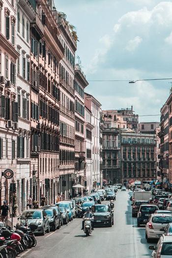 Cars On City Street By Buildings Against Sky