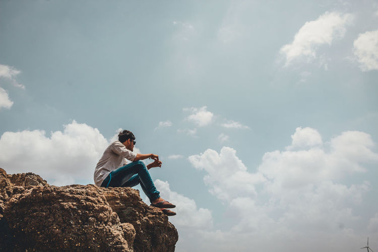 Low Angle View Of Young Man Sitting On Cliff Against Sky