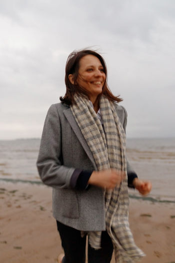Smiling woman standing on beach against sky