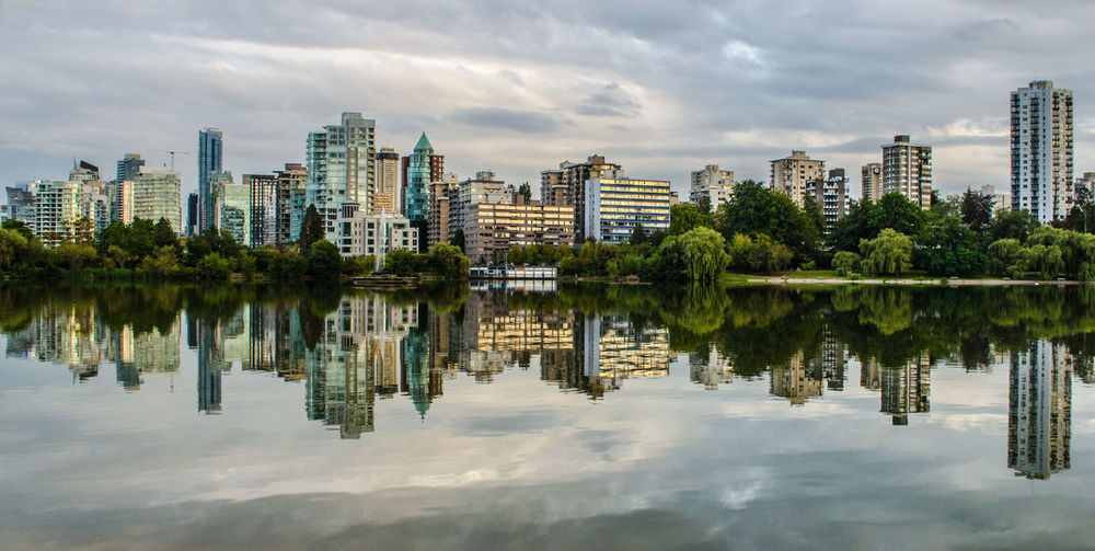 Buildings reflecting on calm lake in city