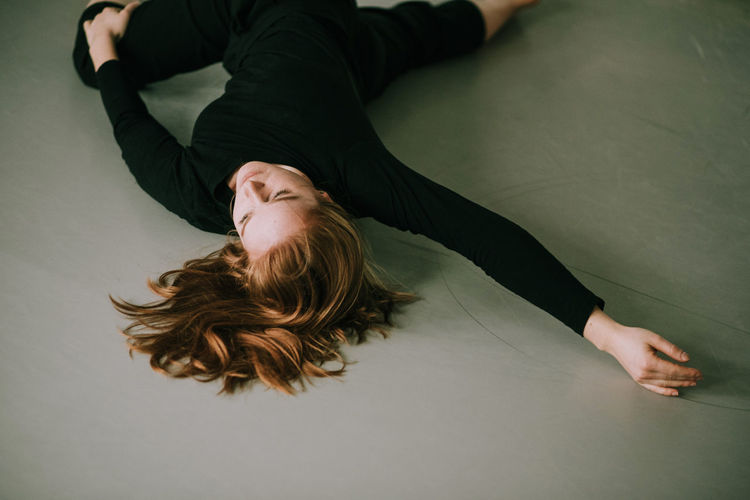 High angle view of woman dancing while lying on floor at home