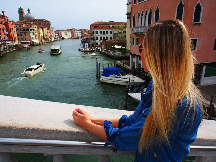 Woman looking at view while standing on bridge over grand canal in city