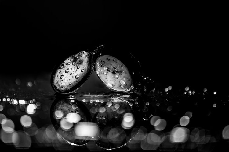 Close-up of water drops on glass against black background