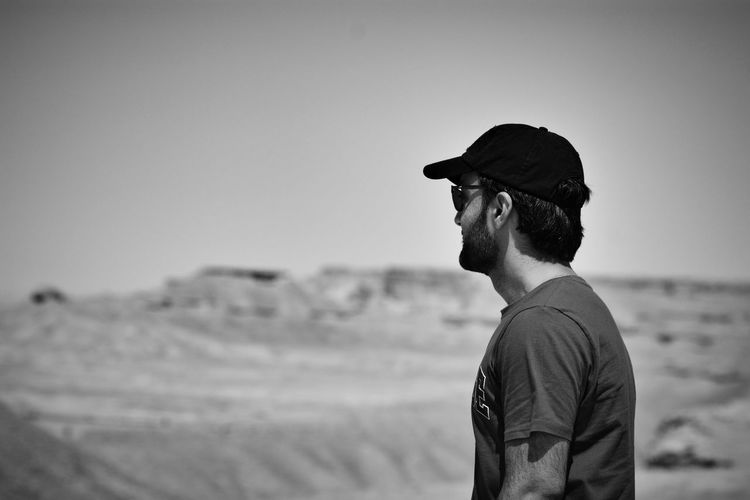 Side view of man looking away against clear sky
