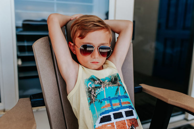 Portrait of boy wearing sunglasses sitting on seat at home