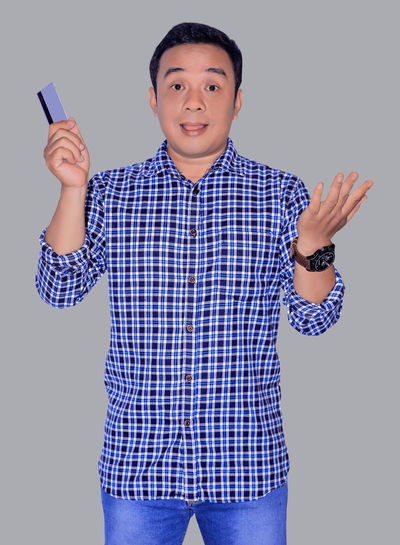 happy man with holding credit card Front View Studio Shot Three Quarter Length Looking At Camera One Person Standing Indoors  Casual Clothing Males  Portrait Men Blue Gesturing Cut Out White Background Young Adult Young Men Lifestyles Human Arm Arms Raised Card Credit Card Payment Bank