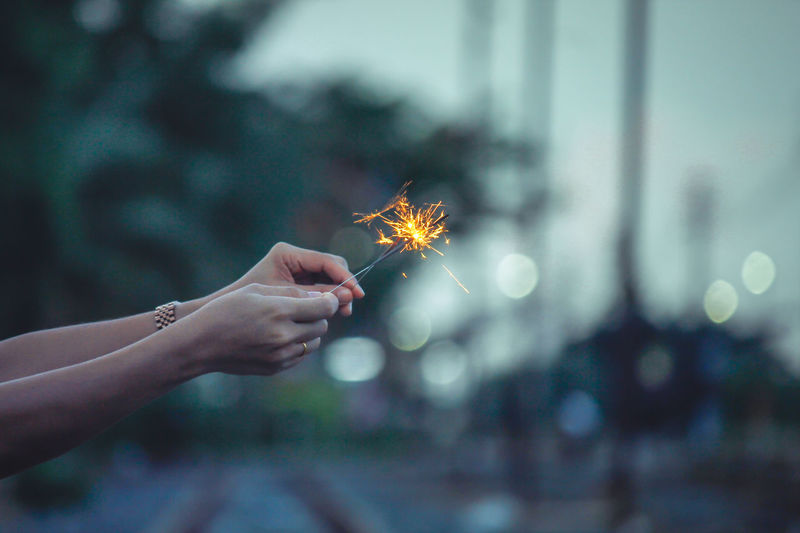 Close-Up Of Woman Hand Holding Illuminated Sparklers
