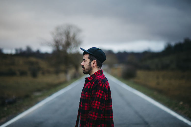 Young man standing on road against sky