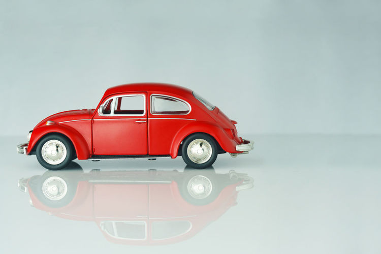 Red toy car against white background