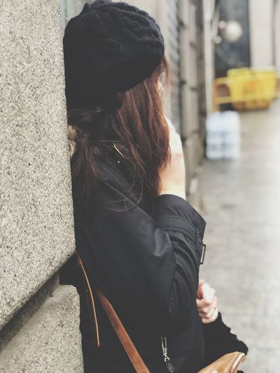 Side view of woman leaning on concrete wall