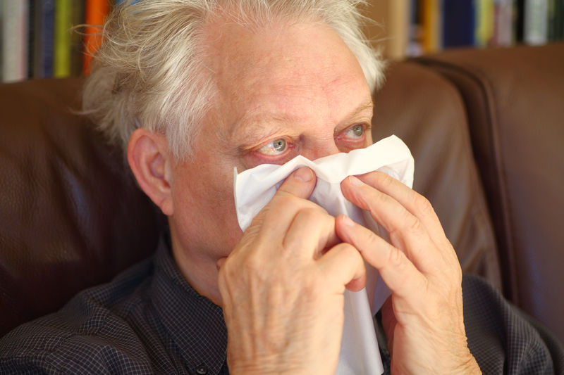 High angle view of senior man wiping nose with tissue while lying on sofa at home