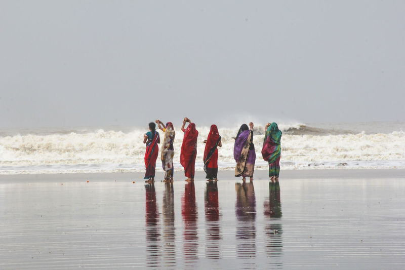 Rear view of women performing rituals while standing on wet shore
